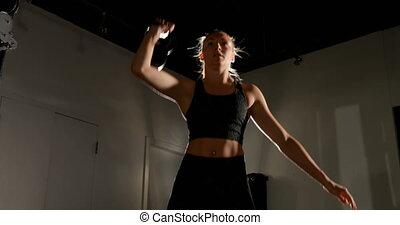 Female athlete exercising with kettlebell 4k