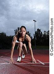 Female athlete in starting position on track - Starting...