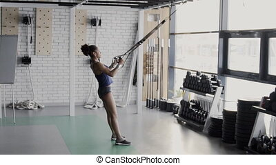 Female athlete is training with trx loops in sports club....