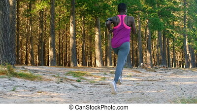 Female athlete jogging in the forest 4k - Rear view of...