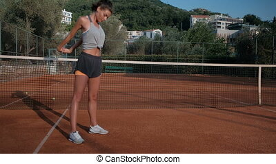 Female athlete makes warm-up standing on stadium in summer day outdoors.