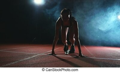 Female athlete on a dark background is preparing to run the...