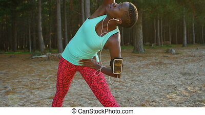 Female athlete performing stretching exercise while...