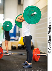 Female Athlete Picking Barbell - Low section of female...