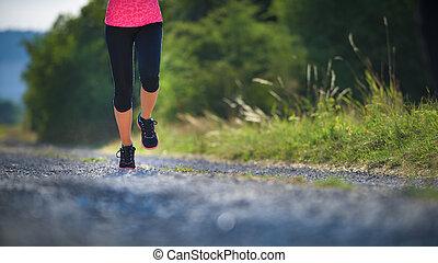 Female athlete runner. closeup on shoe. woman fitness sunset jog workout concept.