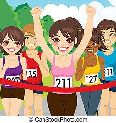 Beautiful brunette female athlete runner woman winning marathon crossing finish line before other runners