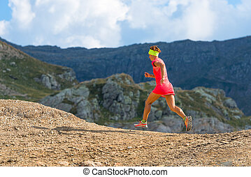 Female athlete runs in the mountains