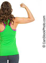 Female athlete showing biceps. rear view