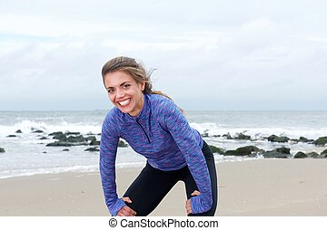 Female athlete standing on beach smiling