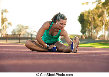female athlete stretching on a running track