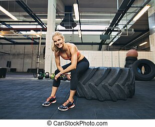 Female athlete taking rest after tough crossfit workout -...