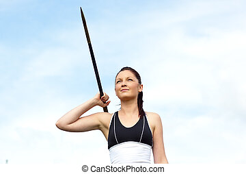 Female athlete throwing the javelin outdoors