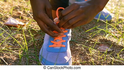 Female athlete tying shoe laces in forest 4k - Close up of...