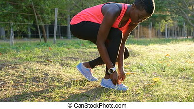 Female athlete tying shoe laces in forest 4k - Young female...