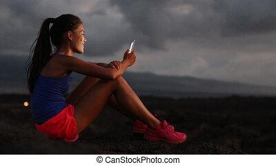 Female Athlete Using Smartphone While Sitting On Arid ...