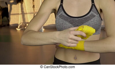 Female athlete wraps elastic bands around arm to reduce risk...
