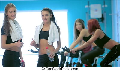 Female athletes girl posing in the gym and look into the camera showing a thumbs