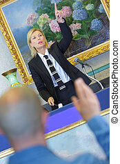 female auctioneer during sale man bidding in the foreground