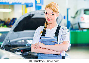 Female auto mechanic working in car workshop