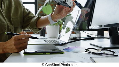 Mid section of Caucasian female automobile engineer using graphics tablet at desk in office. She is sitting at desk 4k