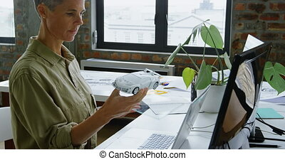 Side view of Caucasian female automobile engineer using graphics tablet and laptop at desk in office. She is sitting at desk 4k