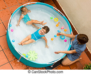 Female baby-sitter with little girls at pool