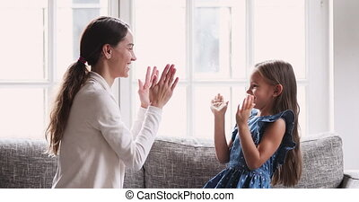 Female babysitter and kid girl playing patty cake at home