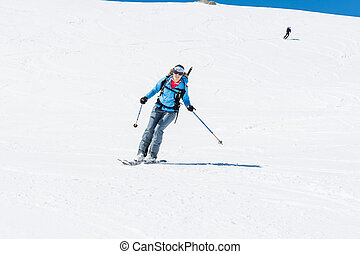 Female back-country skier tackling a steep slope. Ski touring in the mountains.