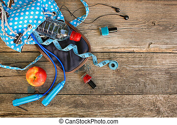 Female backpack with sports equipment, cosmetics, measure tape, water on wooden background.