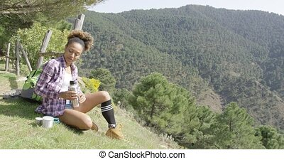 Female backpacker on rest in mountains