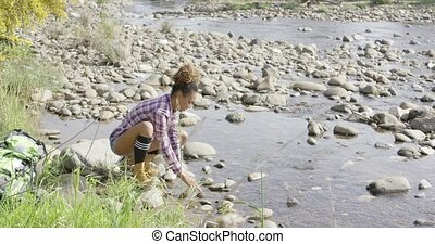 Female backpacker refreshing in creek - Young female...