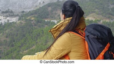 Female backpacker taking a rest - Back of young female...