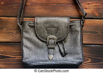 Female bag on a wooden background. Close up