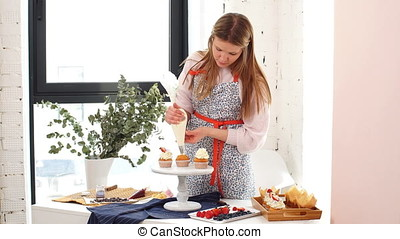 Female baker decorating cupcakes. - Female in mottled dress...
