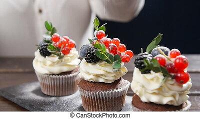 Baker decorating tasty cupcake. Icing sugar sprinkled on cake