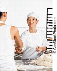 Female Baker Giving Dough To Colleague