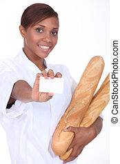 Female baker holding baguettes and a blank business card