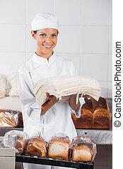 Female Baker Holding Bread Slices In Bakery