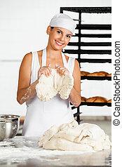 Female Baker Holding Dough At Table