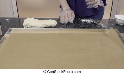 Female baker is rolling small piece of dough on black table at kitchen.