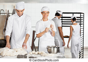 Female Baker Kneading Dough With Colleague In Bakery