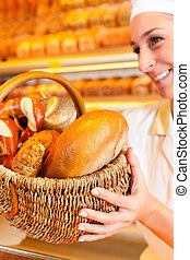 Female baker selling bread by basket in bakery