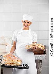 Female Baker Stacking Packed Pizza Breads In Bakery
