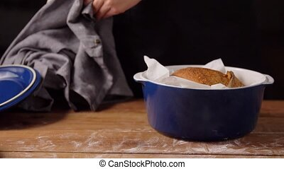 food, cooking and people concept - female baker with loaf of bread in baking dish at bakery or kitchen
