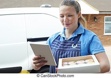 Female Baker With Digital Tablet Making Home Delivery Of...