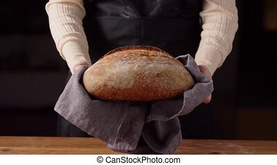 food cooking, baking and people concept - female baker with loaf of bread at bakery or kitchen