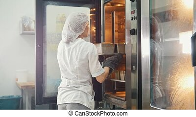 Female bakes on commercial kitchen - pulls the bread from ...