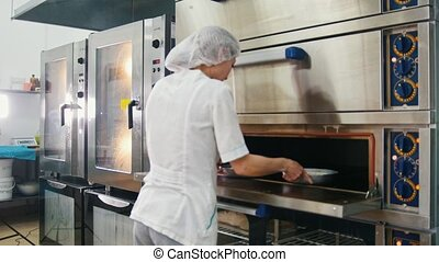 Female bakes on commercial kitchen - woman puts baking in the oven