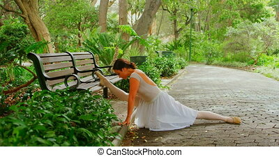 Female ballerina doing stretching exercise in the park 4k
