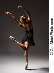 Beautiful young female classical ballet dancer on pointe shoes wearing a black leotard and skirt on a neutral grey studio background